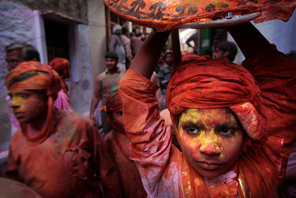 . A young villager from Nandgaon soaked in water and colors arrives in Barsana village during the Lathmar Holy festival, the legendary hometown of Radha, consort of Hindu God Krishna, in Barsana 115 kilometers (71 miles) from New Delhi, India, Thursday, March 21, 2013. During Lathmar Holi the women of Barsana beat the men from Nandgaon, the hometown of Krishna, with wooden sticks in response to their teasing as they depart the town. (AP Photo/Manish Swarup)