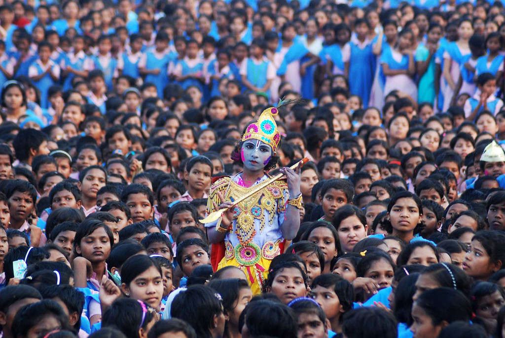 . An Indian schoolchild dressed as the Hindu god Krishna and adorned with colored powder stands among other students during celebrations for the spring festival Holi in Bhubaneswar on March 16, 2014. Holi, the popular Hindu spring festival of colors is observed in India at the end of the winter season on the last full moon of the lunar month.  AFP PHOTO / ASIT KUMAR/AFP/Getty Images