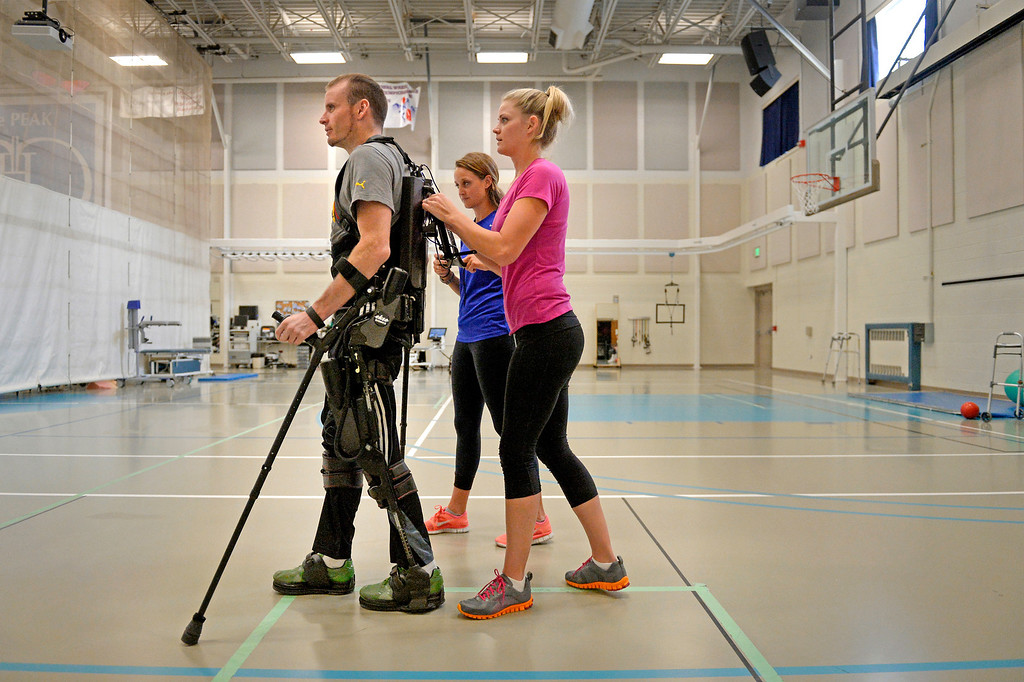 """. An exoskeleton senses a patient\'s intentions by leaning, then helps complete the step. James stood for more than 40 minutes and took 819 steps. \""""As they get smaller and more affordable, I\'d like to see them get into the civilian population and offer that freedom.\"""" (Photo By Craig F. Walker / The Denver Post)"""
