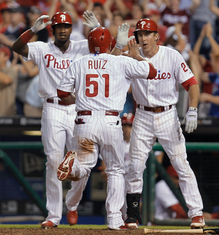 . Philadelphia Phillies\' Carlos Ruiz is cheered by Chase Utley and Domonic Brown after scoring the game-winning run on a hit by Michael Young in the ninth inning in a baseball game against the Colorado Rockies, Wednesday, Aug. 21, 2013, in Philadelphia. The Phillies defeated the Rockies 4-3. (AP Photo/Laurence Kesterson)