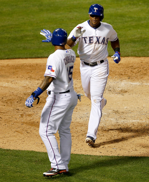 . Texas Rangers\' Michael Choice greets Adrian Beltre, right, at home after Beltre\'s two-run home run that scored Choice off a pitch from Colorado Rockies\' Jorge De La Rosa in the fourth inning of a baseball game, Wednesday, May 7, 2014, in Arlington, Texas. (AP Photo/Tony Gutierrez)