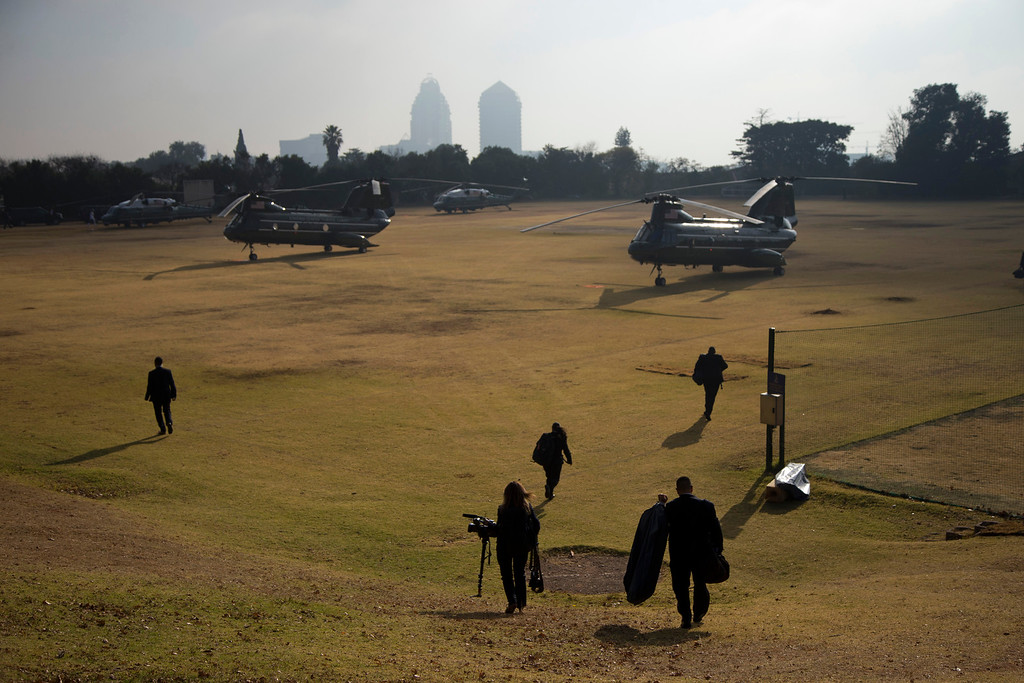 . White House staff walk to helicopters that will bring them to a news conference with U.S. President Barack Obama and South African President Jacob Zuma at the Union Building on Saturday, June 29, 2013, in Sandton, South Africa. The president is in South Africa, embarking on the second leg of his three-country African journey. The visit comes at a poignant time, with former South African president and anti-apartheid hero Nelson Mandela ailing in a Johannesburg hospital. (AP Photo/Evan Vucci)