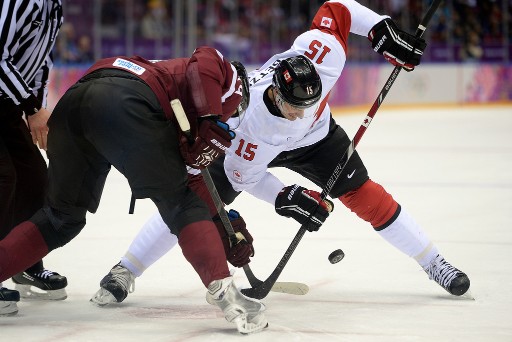 . SOCHI, RUSSIA - FEBRUARY 19: Ryan Getzlaf (15) of the Canada and Vitalijs Pavlovs (79) of the Latvia face off during the first period of men\'s hockey action. Sochi 2014 Winter Olympics on Wednesday, February 19, 2014 at Bolshoy Ice Arena. (Photo by AAron Ontiveroz/ The Denver Post)