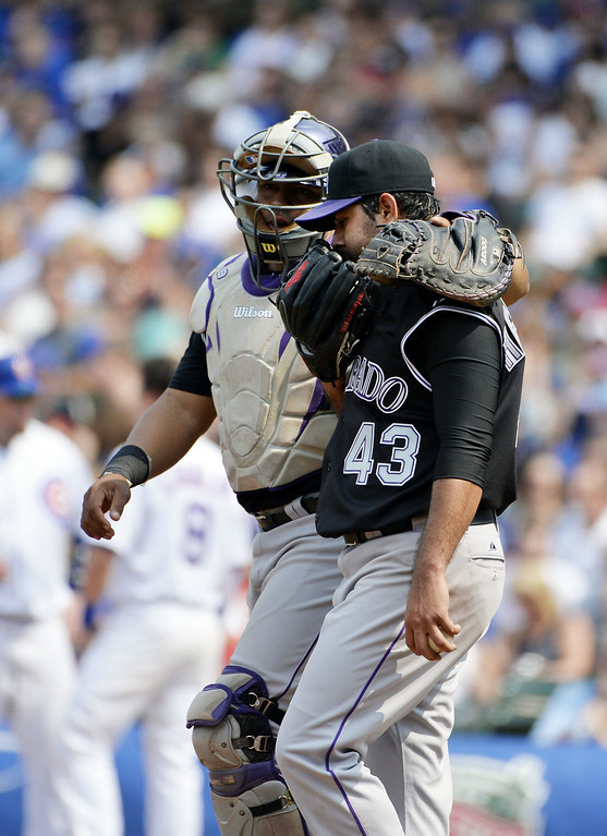 . Catcher Wilin Rosario #20 of the Colorado Rockies (L) talks with starting pitcher Pedro Hernandez #43 during the sixth inning against the Chicago Cubs at Wrigley Field on July 31, 2014 in Chicago, Illinois.  (Photo by Brian Kersey/Getty Images)