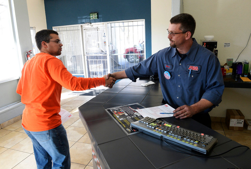 . Active army soldier Luke Goeckner, left, gets a handshake from Mark Prigge, at a Grease Monkey in east Denver, after getting an oil change on his truck, November 11, 2013. Veterans got a free oil change at many Grease Monkey locations for Veterans Day. (Photo By RJ Sangosti/The Denver Post)