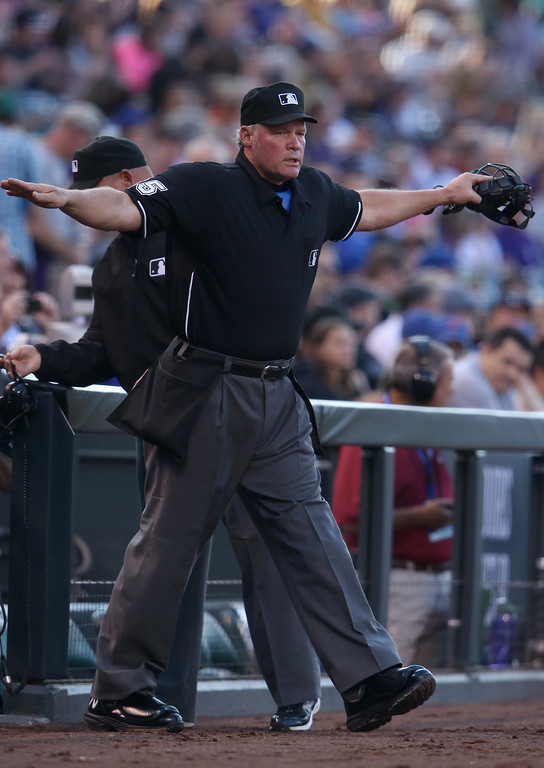 . DENVER, CO - MAY 03:  Umpire crew chief Ted Barrett upholds a safe call on a tag play that was contested by manager Walt Weiss #22 of the Colorado Rockies on Lucas Duda #21 of the New York Mets allowing Chris Young #1 of the New York Mets to score in the first inning at Coors Field on May 3, 2014 in Denver, Colorado.  (Photo by Doug Pensinger/Getty Images)