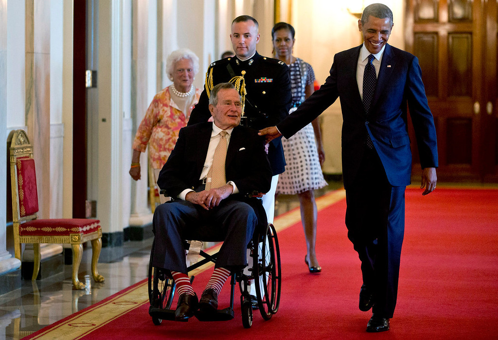 """. President Barack Obama with former President George H. W. Bush, first lady Michelle Obama and former first lady Barbara Bush, behind left, arrive to present the 5,000th Daily Point of Light Award to Floyd Hammer and Kathy Hamilton, a retired couple and farm owners from Union, Iowa,  in the East Room of the White House in Washington, Monday, July 15, 2013. Obama welcomed Bush to the White House in a salute to public service and to the drive for volunteerism that the 41st president inspired with his \""""thousand points of light\"""" initiative more than two decades ago.  (AP Photo/Carolyn Kaster)"""