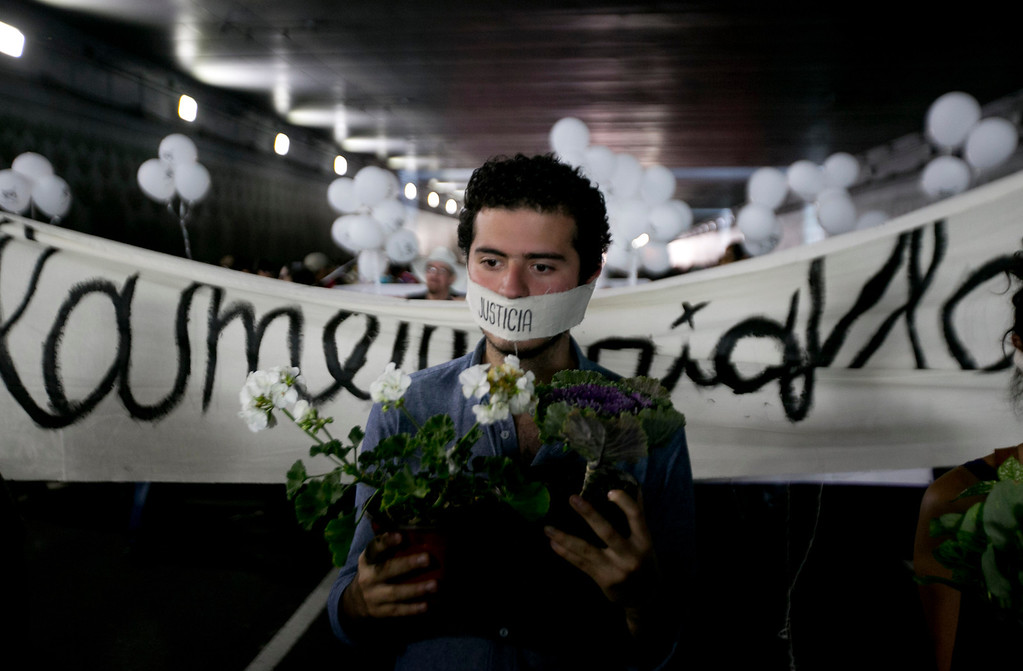 """. A student with his mouth covered with the word \""""Justice\"""" carries flowers during a protest marking the anniversary of the Tlatelolco massacre in Mexico City, Wednesday, Oct. 2, 2013. Mexico commemorated the 45th anniversary of the massacre of students holding an anti-government protest, killed by men with guns and soldiers in 1968 days before the Summer Olympics celebrations in Mexico City. (AP Photo/Eduardo Verdugo)"""