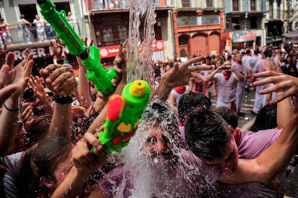 ". Revelers have water thrown on them from a balcony during the launch of the \'Chupinazo\' rocket, to celebrate the official opening of the 2014 San Fermin fiestas, in Pamplona, Spain, Sunday, July 6, 2014. Revelers from around the world kick off the festival with a messy party in the Pamplona town square, one day before the first of eight days of the running of the bulls glorified by Ernest Hemingway\'s 1926 novel ""The Sun Also Rises.\"" (AP Photo/Alvaro Barrientos)"