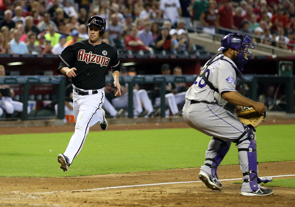 . Aaron Hill #2 of the Arizona Diamondbacks scores a run past catcher Wilin Rosario #20 of the Colorado Rockies during the fifth inning of the MLB game at Chase Field on July 7, 2013 in Phoenix, Arizona.  (Photo by Christian Petersen/Getty Images)