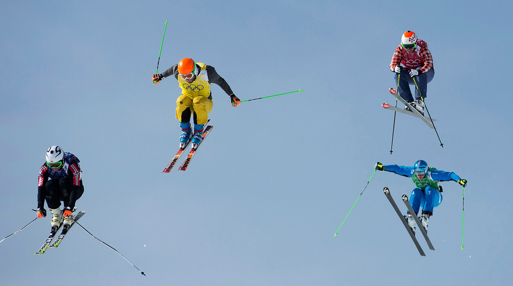 . Men\'s ski cross racers, from left, Didrik Bastian of Norway, Andreas Schauer of Germany, Christopher Delbosco of Canada, and Thomas Zangerl of Austria, fly through the air during the eighth final at the 2014 Winter Olympics at the Rosa Khutor Extreme Park, Thursday, Feb. 20, 2014, in Krasnaya Polyana, Russia. (AP Photo/The Canadian Press, Jonathan Hayward)