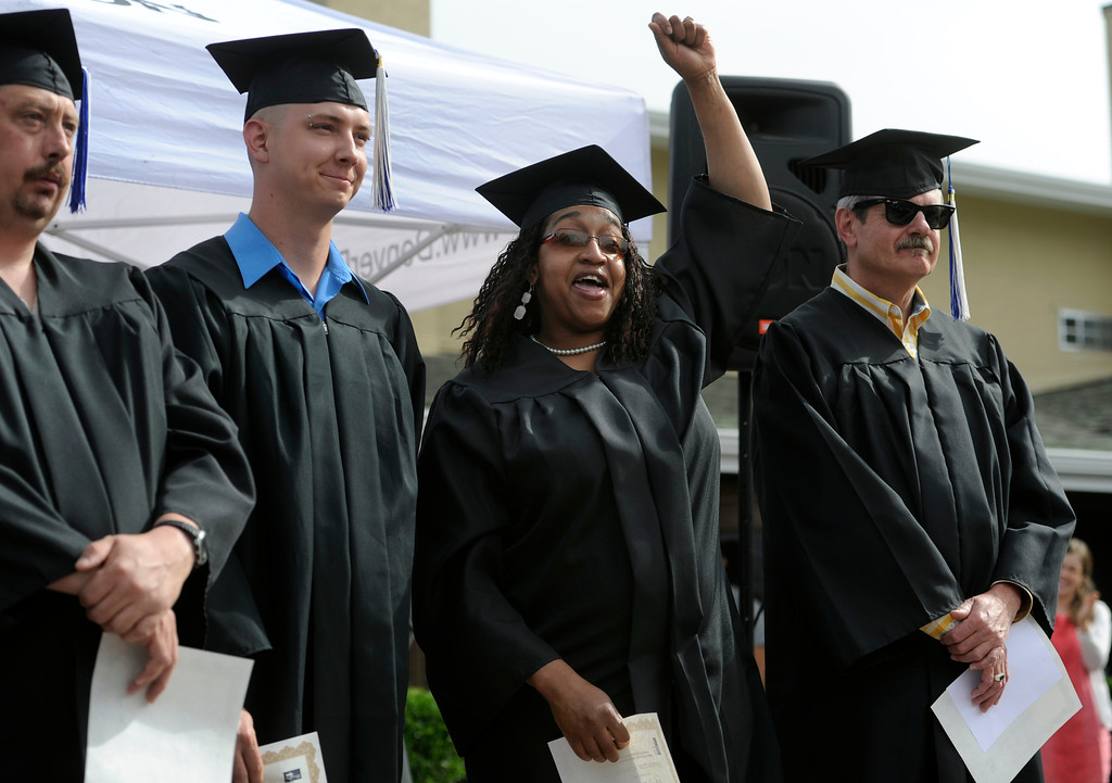 . Flanked by her fellow graduates David Gorry, left, Joshua Fuller, second from left, and Brad Barkey, right, Liberia Flowers raises her hand in a cheer after she receives her certificate. (Photo By Kathryn Scott Osler/The Denver Post)
