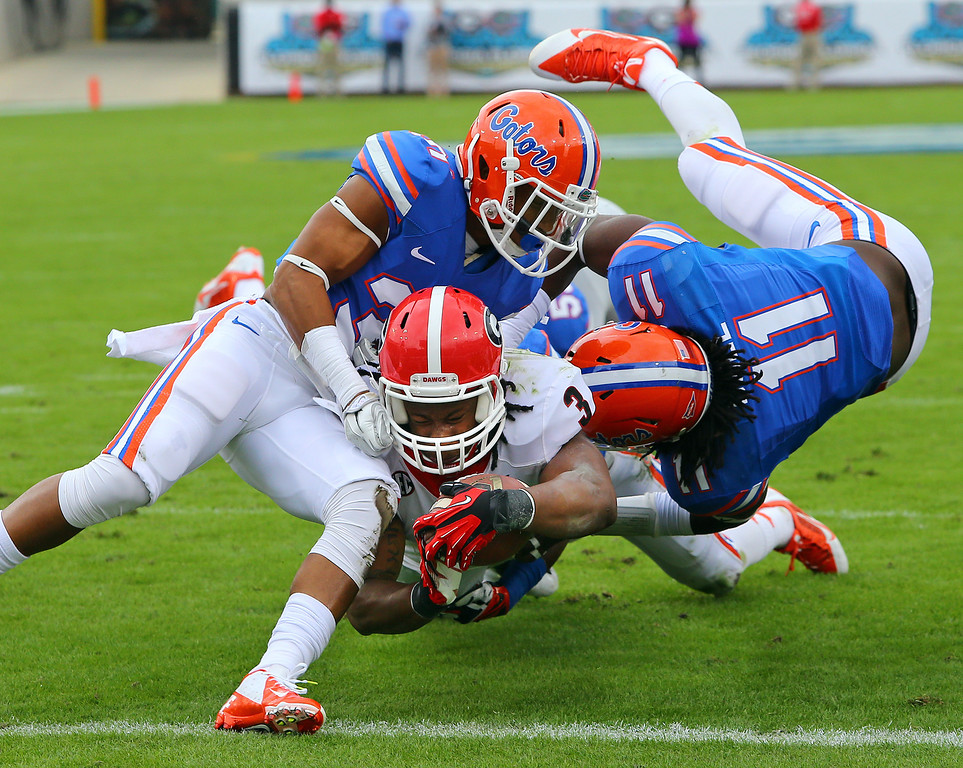 . Georgia tailback Todd Gurley plows his way into the end zone between Florida defenders Cody Riggs, left, and Neiron Ball during the first half of an NCAA college football game in Jacksonville, Fla., Saturday, Nov. 2, 2013. (AP Photo/Atlanta Journal-Constitution, Curtis Compton)