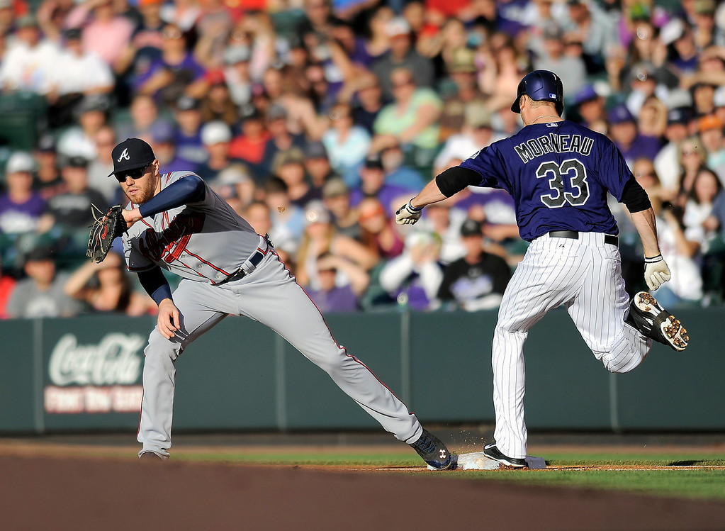 . Atlanta Braves first baseman Freddie Freeman makes the putout on Colorado Rockies Justin Morneau in the first inning of a baseball game on Monday, June 9, 2014, in Denver. (AP Photo/Chris Schneider)