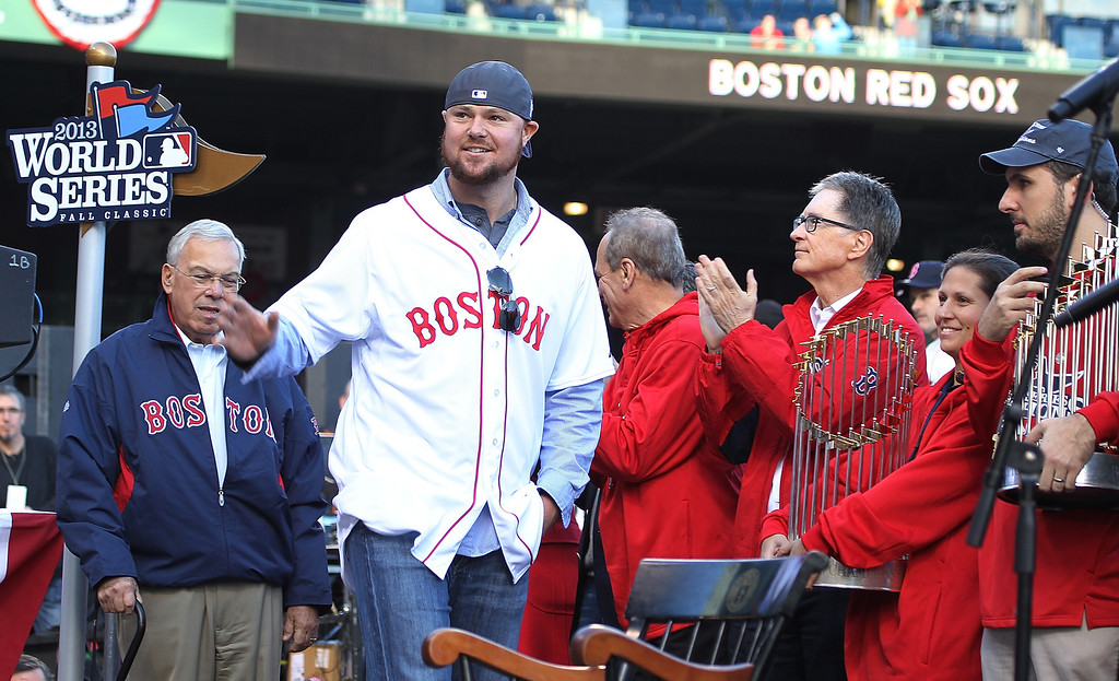 . BOSTON, MA - NOVEMBER 2:  Jon Lester (center) walks on stage as Red Sox principal own John Henry (right) claps at Fenway Park before the Red Sox players board the duck boats for the World Series victory parade for the Boston Red Sox on November 2, 2013 in Boston, Massachusetts.  (Photo by Gail Oskin/Getty Images)