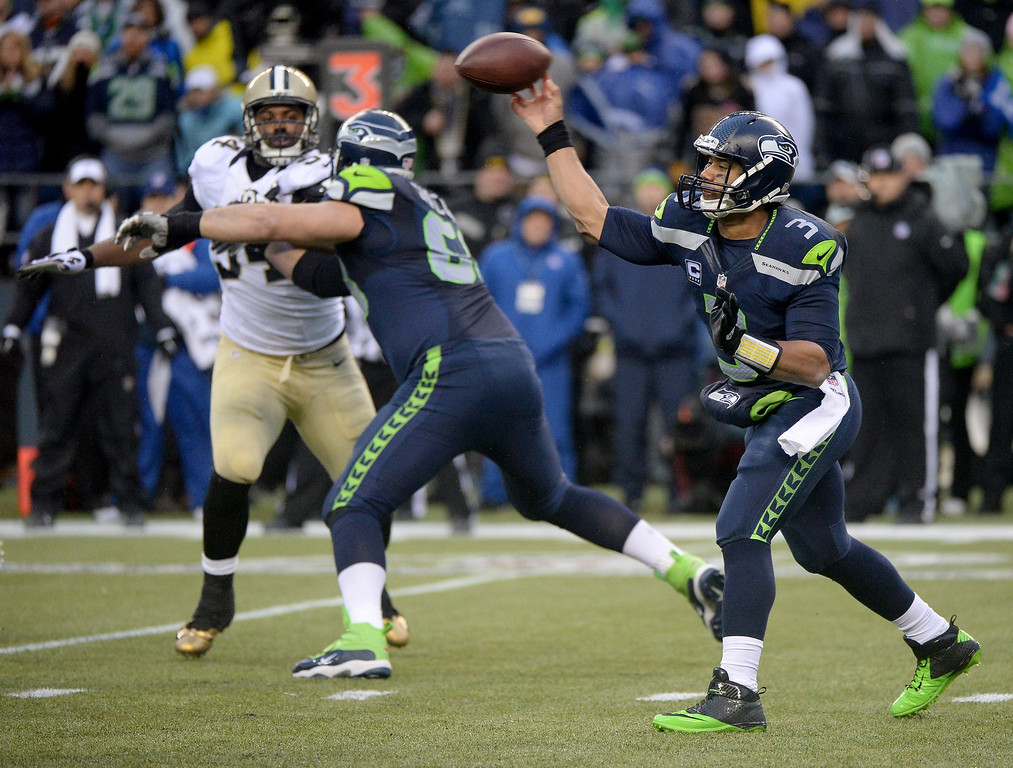 . SEATTLE, WA - JANUARY 11:  Quarterback Russell Wilson #3 of the Seattle Seahawks throws the ball in the fourth quarter while taking on the New Orleans Saints during the NFC Divisional Playoff Game at CenturyLink Field on January 11, 2014 in Seattle, Washington.  (Photo by Harry How/Getty Images)