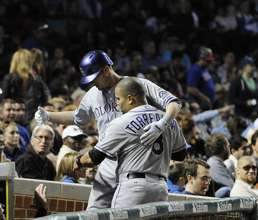 . Reid Brignac #16 of the Colorado Rockies is greeted by Yorvit Torrealba #8 after hitting a home run during the sixth inning against the Chicago Cubs on May 15, 2013 at Wrigley Field in Chicago, Illinois.   (Photo by David Banks/Getty Images)