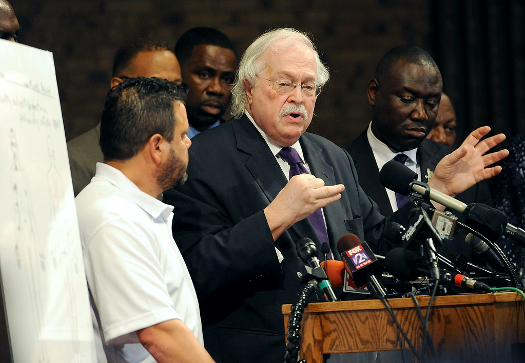 ". Forensic pathologist Michael Baden(C) addresses members of the media concerning the preliminary autopsy report of slain 18 year-old Michael Brown on August 18, 2014 at the Greater St. Marks Family Church in Ferguson, Missouri. Michael Brown, the black teen whose killing by a Missouri police officer has prompted more than a week of unrest, was shot at least six times, pathologists retained by his family said Monday. ""Six bullets struck, and two may have re-entered\"" the 18-year-old\'s body, said Michael Baden, tasked by Brown\'s family and lawyers to conduct an independent examination on his remains. One of the bullets hit the top of Brown\'s head, another struck his eye, while others were located on his right arm, Baden told a press conference.  AFP PHOTO / Michael B. Thomas/AFP/Getty Images"