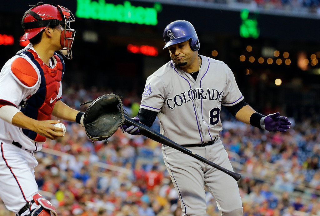 . Colorado Rockies\' Yorvit Torrealba (8) reacts after his strikeout as Washington Nationals catcher Kurt Suzuki prepares to throw the ball, during the fifth inning of a baseball game at Nationals Park, Thursday, June 20, 2013, in Washington. (AP Photo/Alex Brandon)