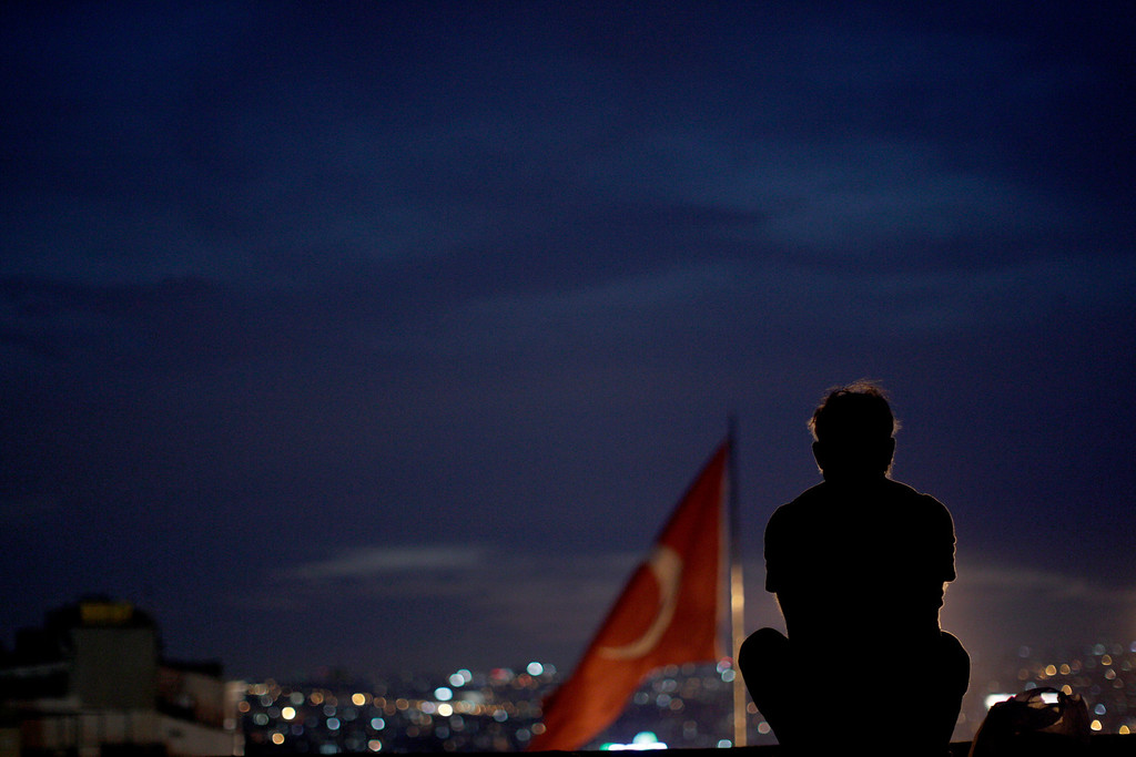 . A man sitting on the roof of Ataturk Cultural center looks at protesters gathered at Taksim square in Istanbul, Tuesday, June 4, 2013.   (AP Photo/Kostas Tsironis)