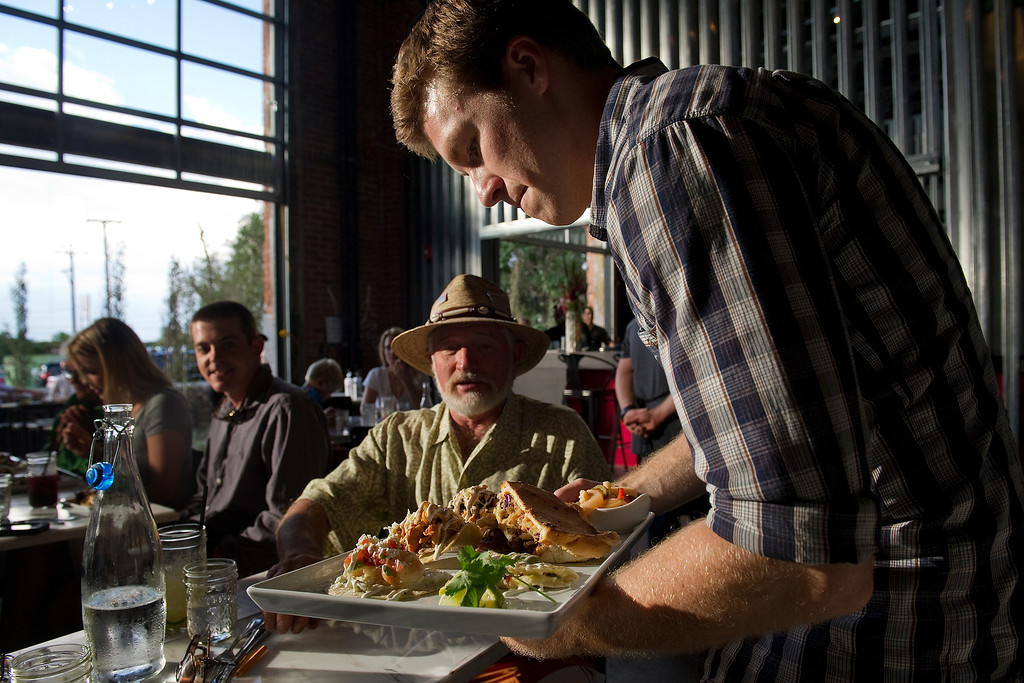 . The new inventive space in a former 19th century foundry, The Source, 3350 Brighton Blvd. in Denver, is beginning to open. The upscale taqueria, Comida, held a soft opening at the location on Monday August 26, 2013. Server Billy Wolfe, right serves Wayne Phipps, center.  (Photo By Cyrus McCrimmon/The Denver Post )