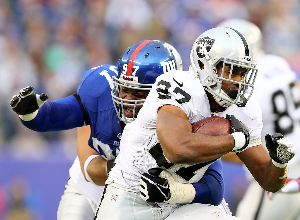 . Rashad Jennings #27 of the Oakland Raiders carries the ball as  Linval Joseph #97 of the New York Giants defends at MetLife Stadium on November 10, 2013 in East Rutherford, New Jersey.  (Photo by Elsa/Getty Images)