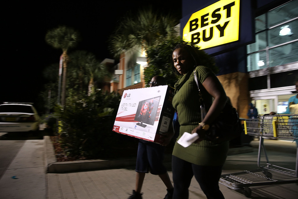 . Black Friday shoppers carry away discounted items from a Best Buy store which opened its doors at 6pm on Thanksgiving Day this year on November 29, 2013 in Naples, Florida. One of the busiest days in the calendar for retailers, over a dozen US stores opened their doors to shoppers one day ahead of the famed-Black Friday shopping day. (Photo by Spencer Platt/Getty Images)