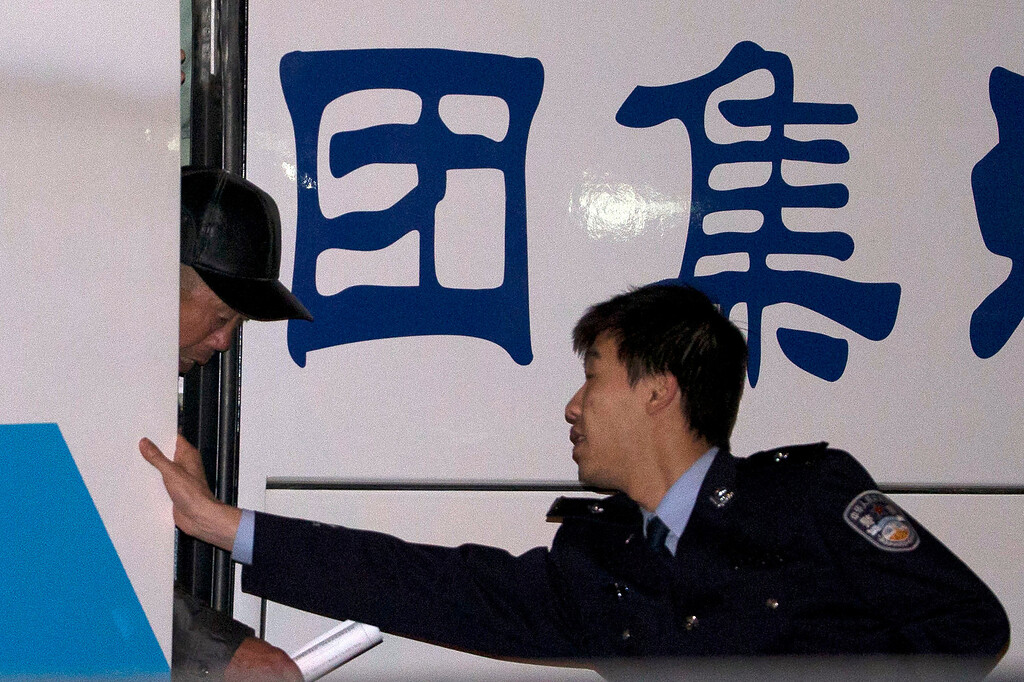 . A Chinese police man helps a relative of Chinese passengers aboard a missing Malaysia Airlines plane as he arrives at the Exit and Entry Administration of the Public Security Bureau, a police department in charge of issuing passports in Beijing, China, Sunday, March 9, 2014. (AP Photo/Ng Han Guan)
