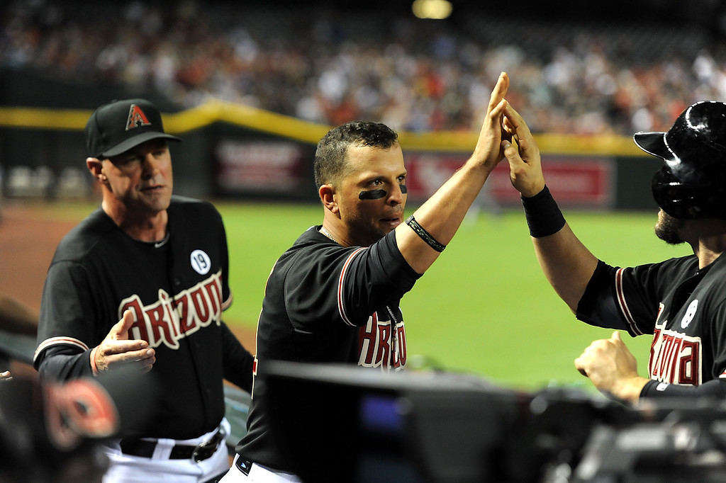 . PHOENIX, AZ - JULY 06:  Martin Prado #14 of the Arizona Diamondbacks celebrates with teammate Didi Gregorius #1 after scoring three runs in the second inning against the Colorado Rockies at Chase Field on July 6, 2013 in Phoenix, Arizona.  (Photo by Norm Hall/Getty Images)