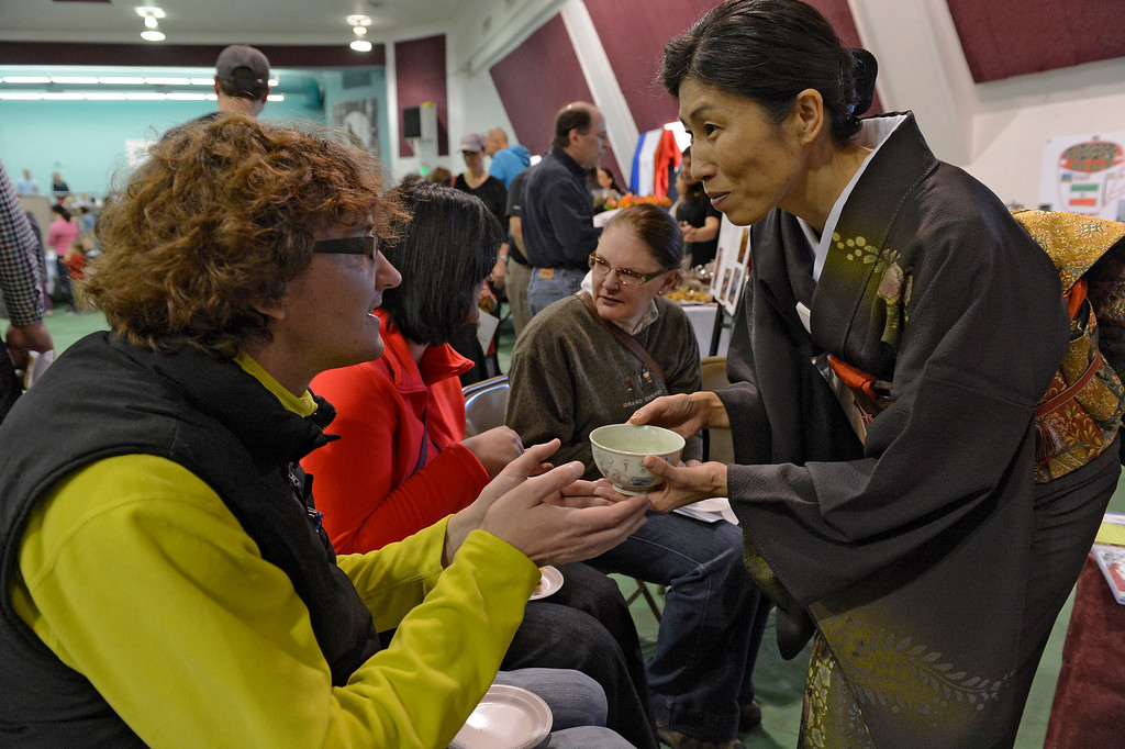 . DENVER, CO. - JANUARY 27: Kyoko Nakagawa hands a cup of tea to Jacob Bentley 33-years old during a traditional  Japanese tea ceremony at the World Tea Fair held at Denver Montclair International School January 27, 2013.  There were 12 tables featuring tea samples from around the World.Photo By John Leyba / The Denver Post)