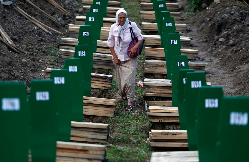 . A Bosnian woman searches for her relative after 409 coffins of newly identified victims from the 1995 Srebrenica massacre were uncovered, in Potocari Memorial Center, near Srebrenica July 10, 2013. The bodies of the recently identified victims will be buried on July 11 marking the 18th anniversary of the massacre in which Bosnian Serb forces commanded by Ratko Mladic killed up to 8,000 Muslim men and boys and buried them in mass graves. REUTERS/Dado Ruvic