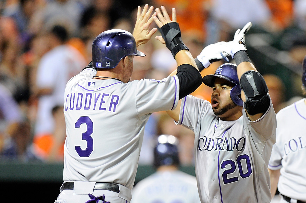 . BALTIMORE, MD - AUGUST 16:  Wilin Rosario #20 of the Colorado Rockies celebrates with Michael Cuddyer #3 after hitting a home run in the seventh inning against the Baltimore Orioles at Oriole Park at Camden Yards on August 16, 2013 in Baltimore, Maryland.  (Photo by Greg Fiume/Getty Images)