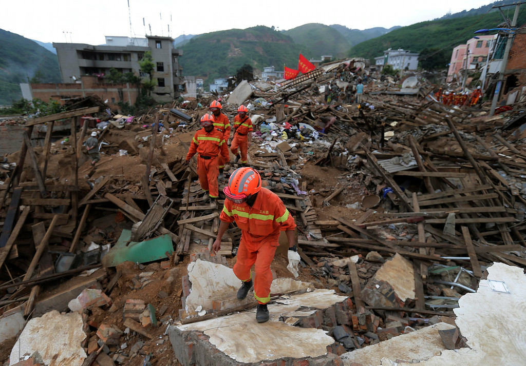 . Rescuers walk through rubbles from destroyed houses as they search for survivors following a massive earthquake in the town of Longtoushan in Ludian County in southwest China\'s Yunnan Province Tuesday, Aug. 5, 2014. (AP Photo/Andy Wong)