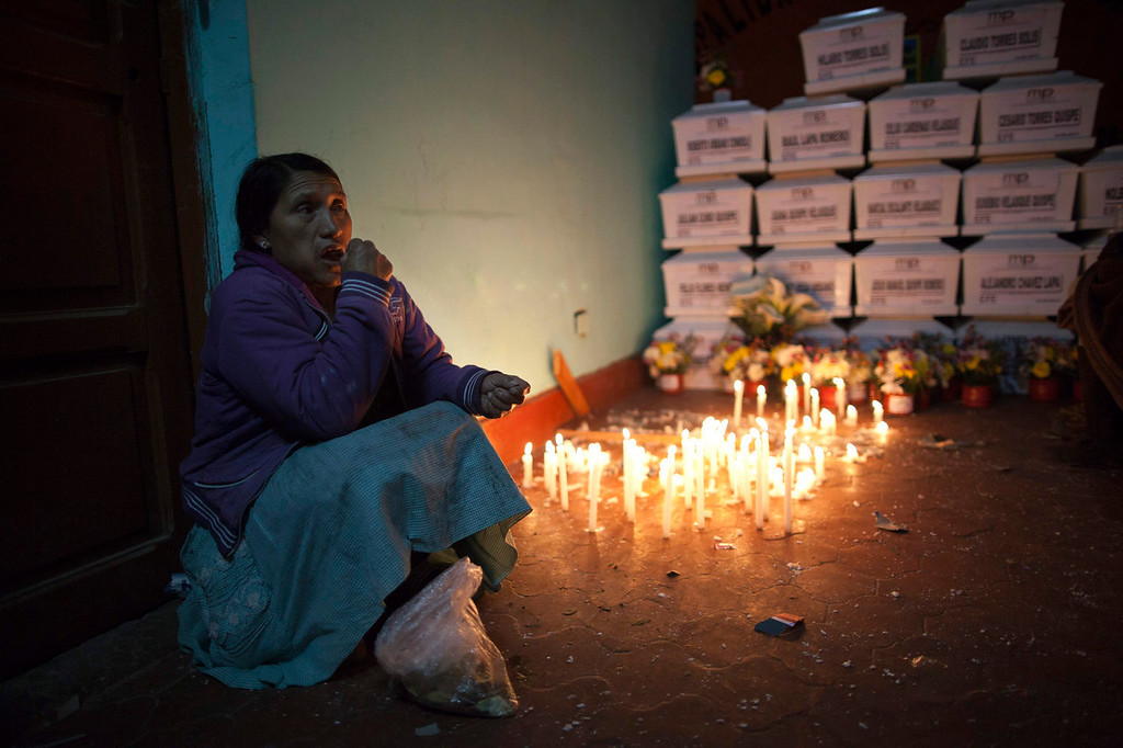 . Rosa Sandoval chews on coca leaves as she keeps vigil next to the coffins that contain the remains of the victims of the 1988 Chaca massacre in San Miguel, Peru. Judges have not accepted that in Peru there were systematic violations of human rights.   (AP Photo/Rodrigo Abd)
