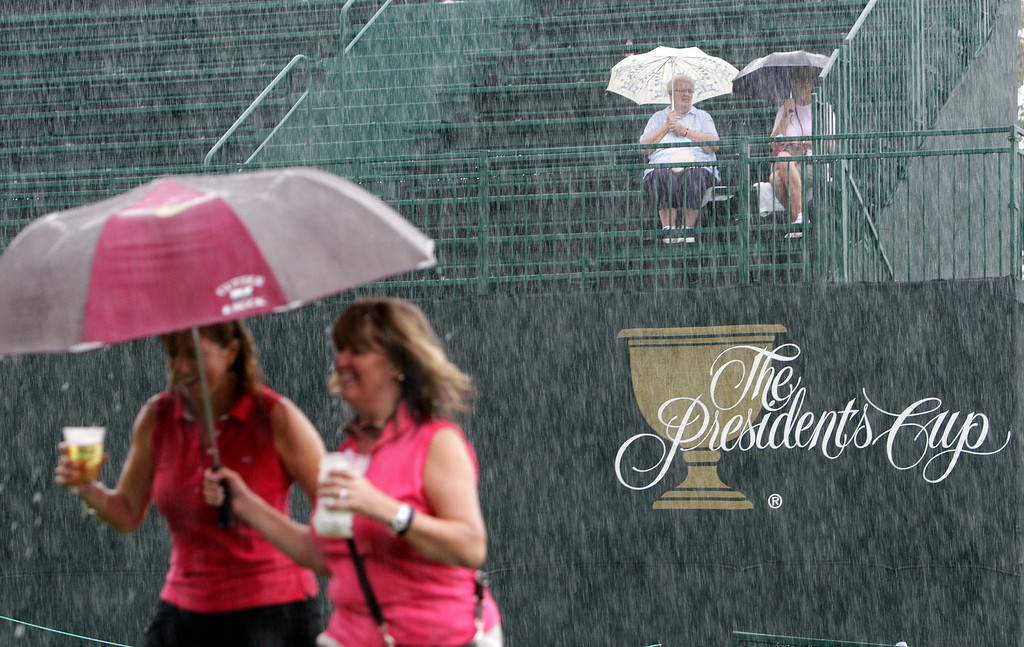 . Fans brave the rain during a weather delay at the Presidents Cup golf tournament at Muirfield Village Golf Club Friday, Oct. 4, 2013, in Dublin, Ohio. (AP Photo/Jay LaPrete)