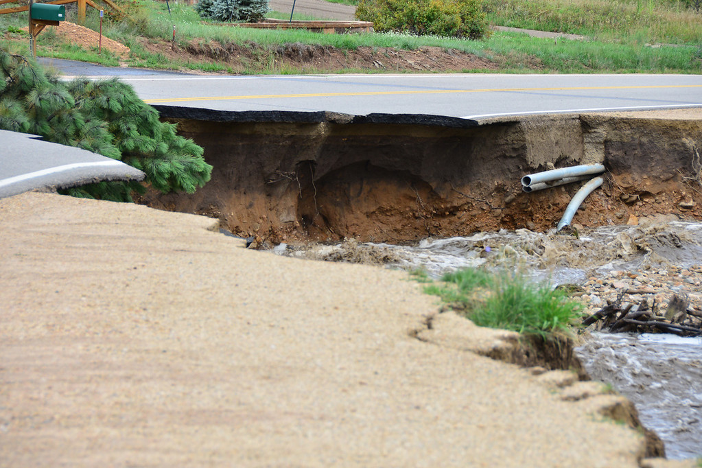 . Broken pipes are exposed where Fish Creek has washed out the Fish Creek Road near the road\'s intersection with Sandborn in Carriage Hills. John Cordsen/Estes Park Trail-Gazette