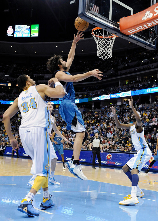 . Minnesota Timberwolves guard Ricky Rubio, center, drives to the basket past Denver Nuggets center JaVale McGee, left, and forward Corey Brewer, right, in the first quarter of an NBA basketball game on Saturday, March 9, 2013, in Denver.  (AP Photo/Chris Schneider)