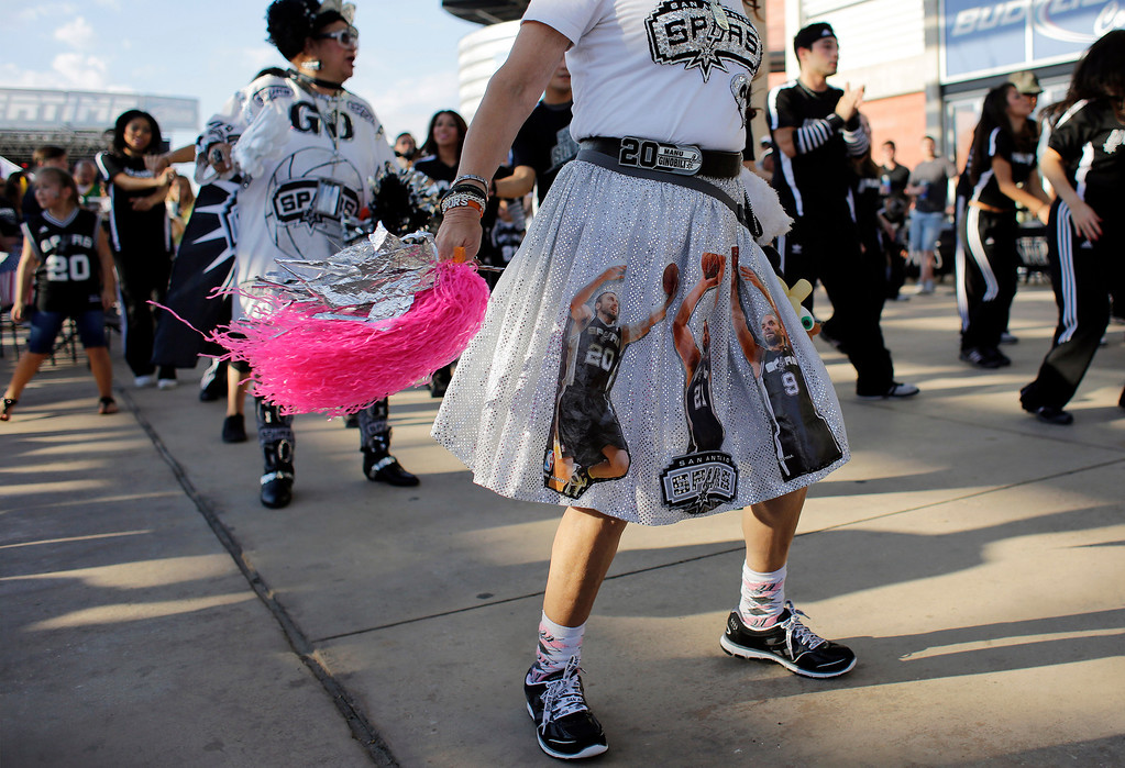 . San Antonio Spurs fans Mary Lou Rodriguez, front, and Sovia Lauflano, left, dance outside the AT&T Center prior to Game 5 of the Western Conference finals NBA basketball playoff series between the Spurs and the Oklahoma City Thunder, Thursday, May 29, 2014, in San Antonio. (AP Photo/Eric Gay)