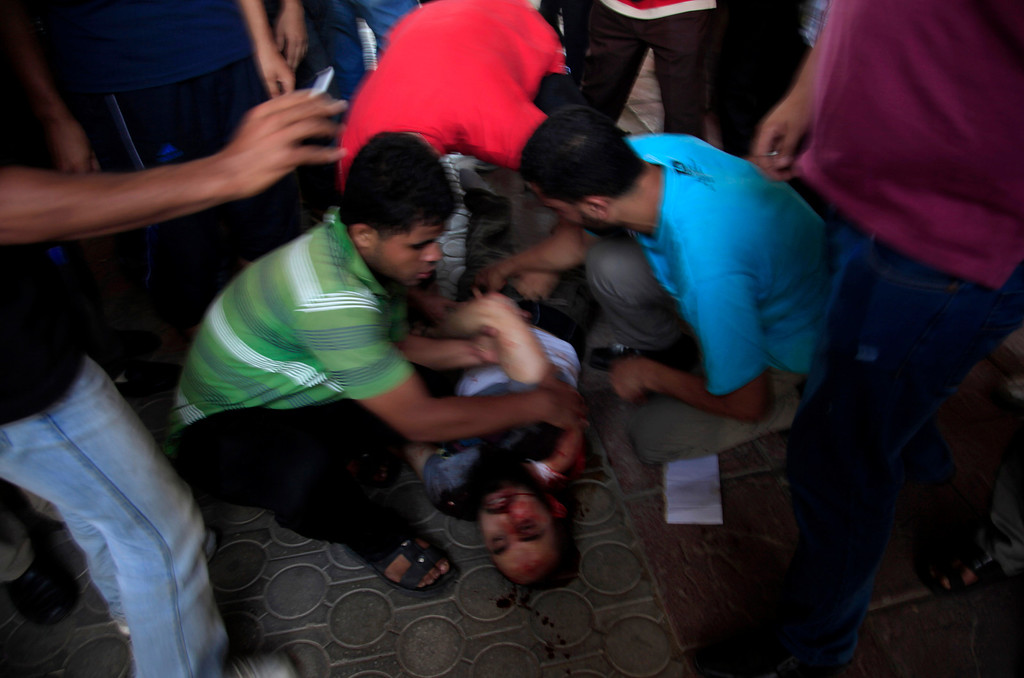 ". People surround the body of a man shot by Egyptian security forces who opened fire on supporters of ousted President Mohammed Morsi in Cairo, Egypt, Friday, July 5, 2013. Egyptian troops opened fire on mostly Islamist protesters marching on a Republican Guard headquarters Friday to demand the restoration of ousted President Mohammed Morsi, killing at least one. The shooting came as tens of thousands of his supporters chanting ""down with military rule\"" rallied around the country. (AP Photo/Khalil Hamra)"