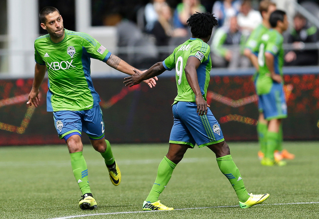 . Seattle Sounders\' Clint Dempsey, left, slaps hands with Sounders\' Obafemi Martins, right, as Dempsey leaves the pitch during the second half of an MLS soccer match against the Colorado Rapids, Saturday, April 26, 2014, in Seattle. Dempsey had two goals and Martins had one as the Sounders won 4-1. (AP Photo/Ted S. Warren)
