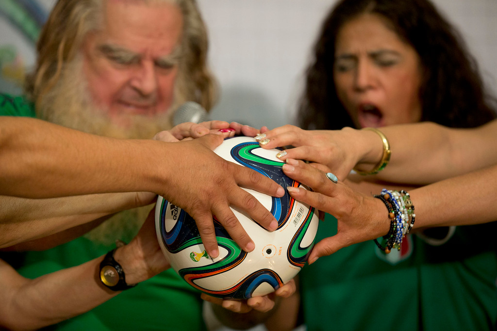 """. Mexico City\'s \""""Great Warlock\"""" Antonio Vazquez, left, and assistants perform a magic ritual using a soccer ball to help Mexico\'s national soccer team reach the quarter-finals in the World Cup, in Mexico City, Wednesday, June 11, 2014. The ceremony was intended to \""""clean\"""" the Mexican team of bad vibes and to \""""neutralize\"""" mystical rituals performed on behalf of the Cameroonian team. (AP Photo/Rebecca Blackwell)"""