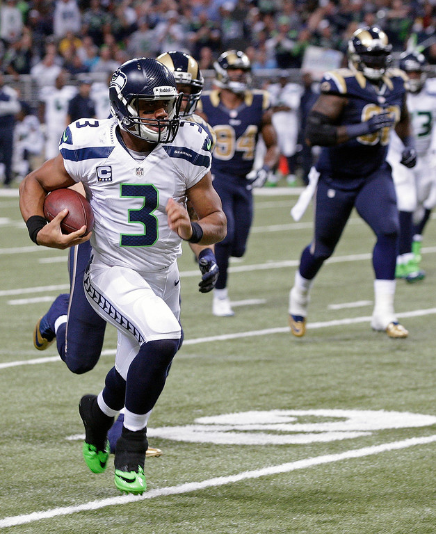 . Seattle Seahawks quarterback Russell Wilson (3) rushes against St. Louis Rams defense during the first half of an NFL football game, Monday, Oct. 28, 2013, in St. Louis. (AP Photo/Tom Gannam)