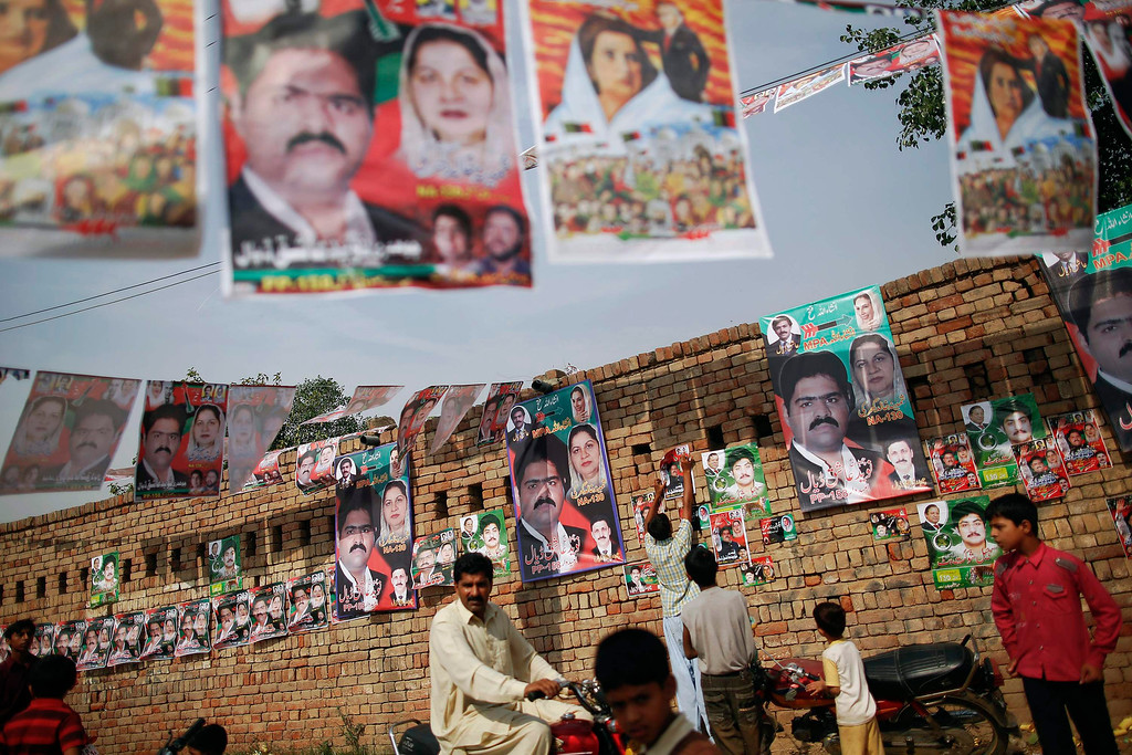 . People gather near a polling station in a village near Lahore May 11, 2013. A string of militant attacks cast a long shadow over Pakistan\'s general election on Saturday, but millions still turned out to vote in a landmark test of the troubled country\'s democracy.  REUTERS/Damir Sagolj