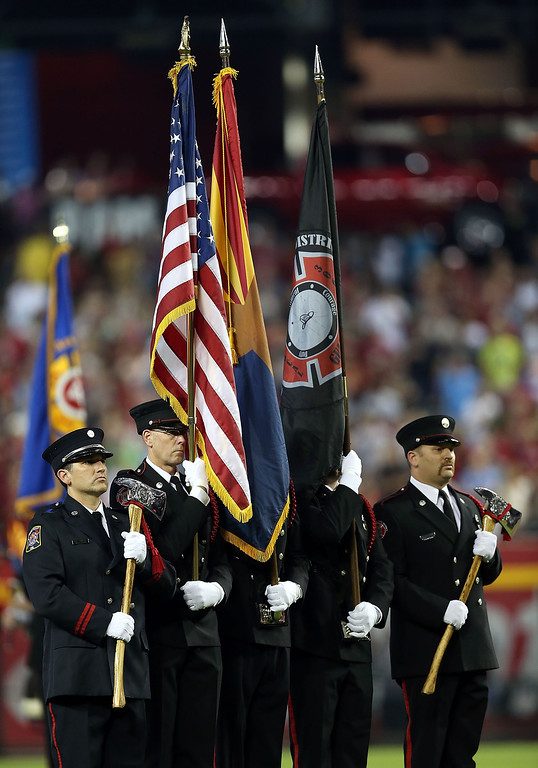 """. PHOENIX, AZ - JULY 05:  The Arizona Joint Fire Fighters Honor Guard stand on the field in honor of the 19 Granite Mountain Interagency Hotshot Crew firefighters who died battling a fast-moving wildfire near Yarnell, AZ before the MLB game between the Arizona Diamondbacks and the Colorado Rockies at Chase Field on July 5, 2013 in Phoenix, Arizona. The Arizona Diamondbacks are wearing a \""""19\"""" patch in honor of  (Photo by Christian Petersen/Getty Images)"""