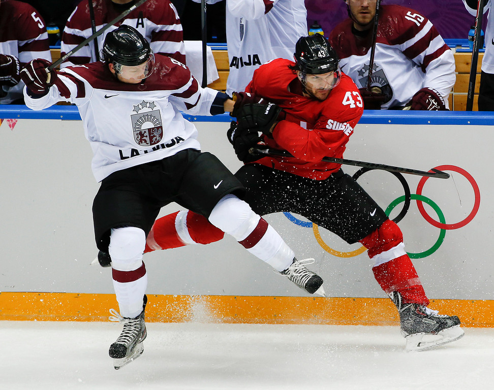 . Latvia forward Ronalds Kenins, left, and Switzerland forward Morris Trachsler crash the boards in the second period of a men\'s ice hockey game at the 2014 Winter Olympics, Tuesday, Feb. 18, 2014, in Sochi, Russia. (AP Photo/Julio Cortez)