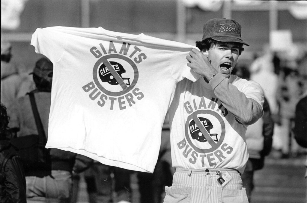 ". JAN 21 1987 - Bruce Borie came in from Los Angles last week to sell Giant Buster"" t-shirts in Denver, and to get ahold of some Super Bowl tickets for he and his friends back in California. He was hawking his t-shirts Sunday at the Bronco Rally held in Mile-High. (Dennis Chamberlin/The Denver Post)"