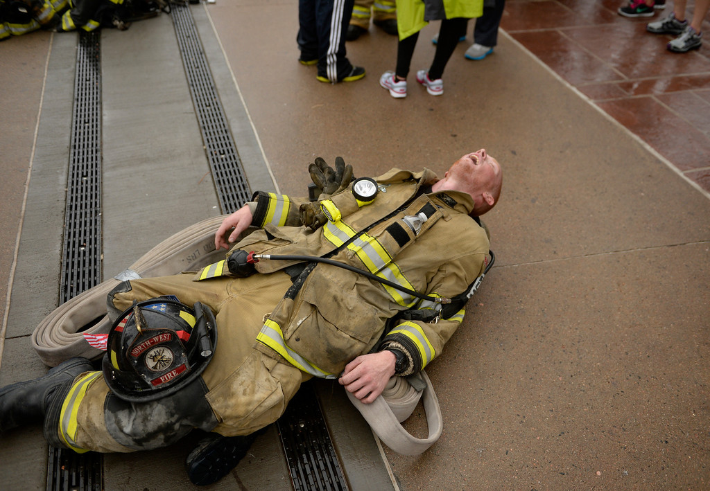 . Zach Poore, of North-West Fire Protection District in Fairplay, falls over in exhaustion after finishing the 911 Stair Climb Red Rocks Amphitheater, September 11, 2013.  (Photo By RJ Sangosti/The Denver Post)