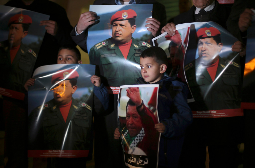 . Palestinian hold posters depicting Venezuela\'s late president Hugo Chavez during a vigil outside the Venezuelan consulate in the West Bank city of Ramallah March 6, 2013. Chavez supported the Palestinian statehood aspirations. REUTERS/Mohamad Torokman