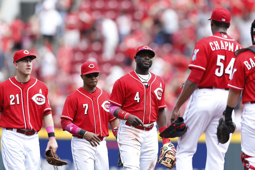 . Todd Frazier #21, Ramon Santiago #7 and Brandon Phillips #4 of the Cincinnati Reds congratulate Aroldis Chapman #54 after the game against the Colorado Rockies at Great American Ball Park on May 11, 2014 in Cincinnati, Ohio. The Reds won the game 4-1. (Photo by Joe Robbins/Getty Images)