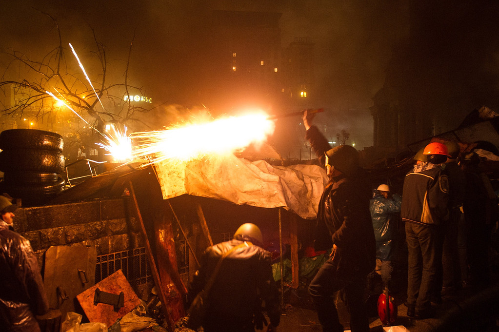 . Anti-government protesters stand behing barricades as they clash with police in the center of Kiev on February 20, 2014. At least 25 protesters were killed on February 20 in fresh clashes between thousands of demonstrators and heavily-armed riot police in the heart of Kiev, AFP correspondents at the scene said. The bodies of eight demonstrators were lying outside Kiev\'s main post office on Independence Square, an AFP reporter said. The bodies of 17 other demonstrators with apparent gunshot wounds were also seen in the vicinity of two hotels on opposite sides of the protest encampment. AFP PHOTO/ VOLODYMYR  SHUVAYEV/AFP/Getty Images